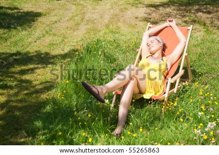 Young woman sitting in a deck chair on a meadow full with flowers.
