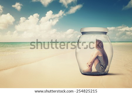 young woman sitting in a glass jar on a beach looking at the ocean view. Loneliness outlier person. After storm survivor message to future generation concept  - stock photo