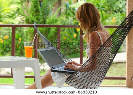 Young woman sitting in a hammock in a garden and typing something on a laptop - stock photo