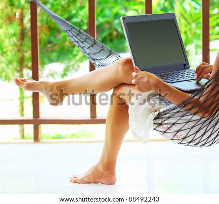 Young woman sitting in a hammock in garden with laptop