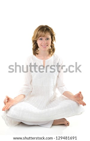 Young woman sitting in a meditative pose on a white background - stock photo