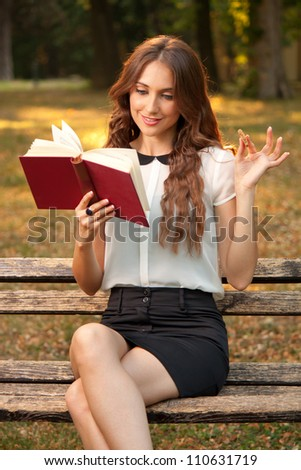 Young woman sitting in a park and reading a book - stock photo
