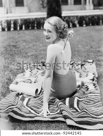 Young woman sitting  in a sun suit on a lawn scratching her back - stock photo