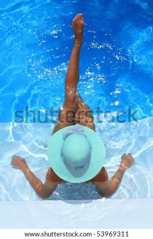 young woman sitting in a swimming pool - stock photo