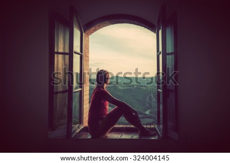 Young woman sitting in an open old window looking on the landscape of Tuscany, Italy. Conceptual romantic, dreaming, hope, travel. - stock photo