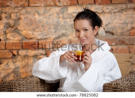 Young woman sitting in armchair in bathrobe, having tea, smiling at camera.?