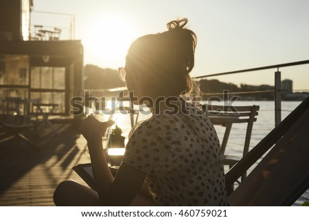 Young woman sitting in cafe and watching the river at summer sunset. Retro style image.