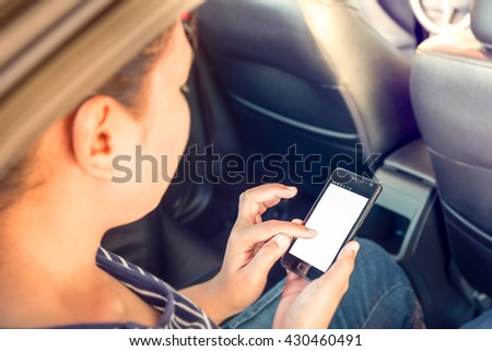 Young woman sitting in car and touch the screen of phone mobile with isolated screen - vintage style color effect  (focus on phone mobile) - stock photo