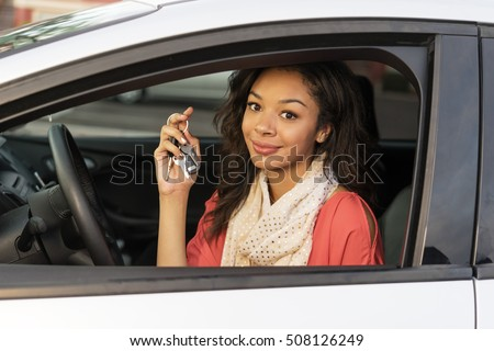 Young woman sitting in car holding keys