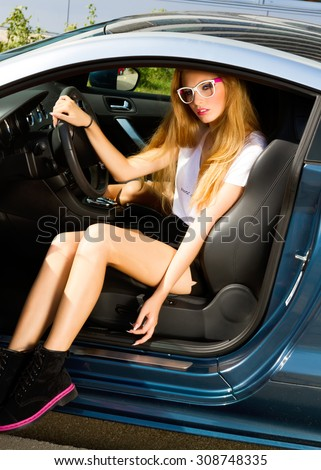 Young woman sitting in car.Portrait of Young sexy blondy student girl sitting driver seat in luxury blue sport car.Slim cute blondy woman inside black leather chair auto open door.steering wheel - stock photo