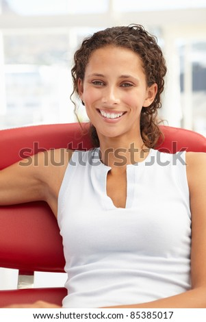 Young woman sitting in chair - stock photo