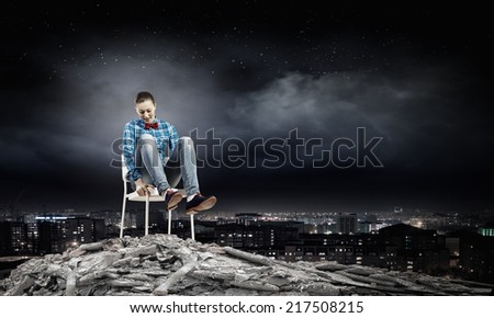 Young woman sitting in chair on ruins - stock photo