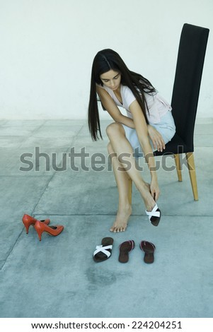 Young woman sitting in chair, trying on pair of shoes, full length portrait - stock photo
