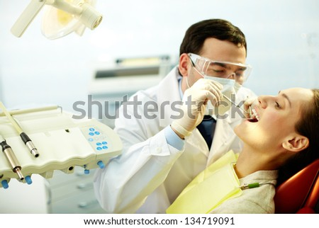 Young woman sitting in dentist�¢??s chair while doctor examining her teeth - stock photo