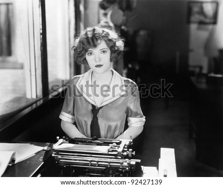 Young woman sitting in front of a typewriter - stock photo