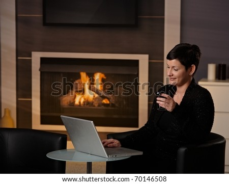 Young woman sitting in front of fireplace at home on a cold winter day, working on laptop computer.? - stock photo
