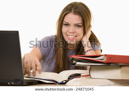 Young woman sitting in front of laptop beside a pile of thick textbooks while reading one with a content expression