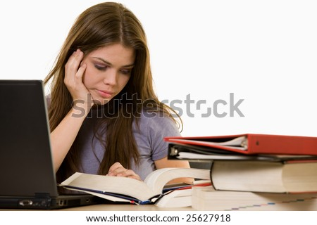 Young woman sitting in front of laptop beside a pile of thick textbooks while reading one with a frustrated stressed expression - stock photo