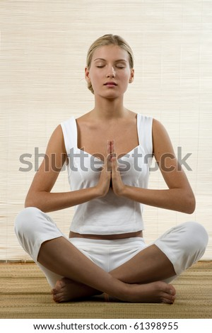 Young woman sitting in lotus position and meditating - stock photo