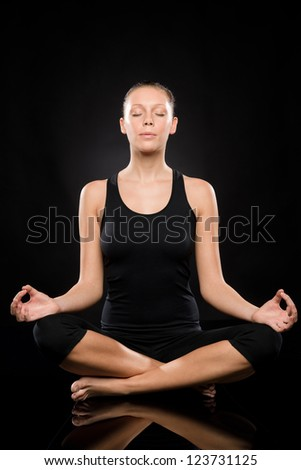 Young woman sitting in lotus position meditating with eyes closed - stock photo