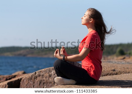 Young Woman sitting in lotus position on rock by the sea - stock photo