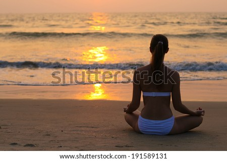 Young woman sitting in lotus position on the sunset beach  - stock photo