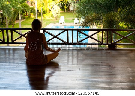 Young woman sitting in lotus position with the balcony looking at the pool in the spa resort - stock photo