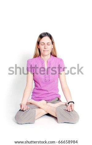 Young woman sitting in lotus seat practicing yoga - stock photo