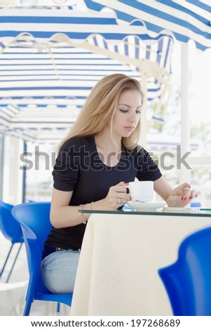 Young woman sitting in outside street cafe with cup of coffee