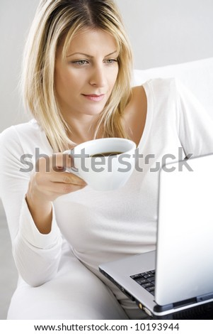 young woman sitting in the couch with a cup of coffee and laptop