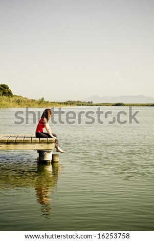 Young woman sitting in the dock of the bay - stock photo