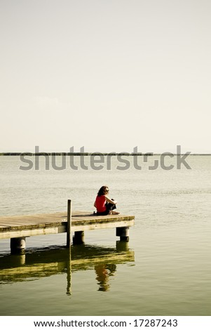 Young woman sitting in the dock of the bay
