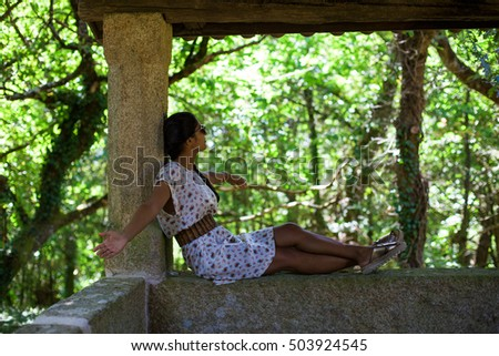 young woman sitting in the forest