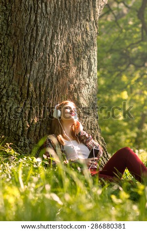 Young woman sitting in the park and listening the music - stock photo