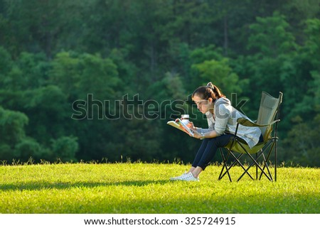 Young woman sitting in the park reading a book and holding paper coffee cup - stock photo