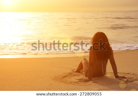 Young woman sitting in the sand looking at the sea at sunset - stock photo