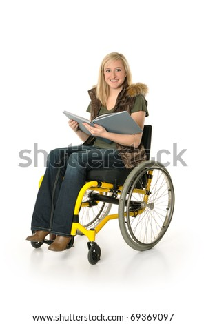 Young woman sitting in wheelchair with a book