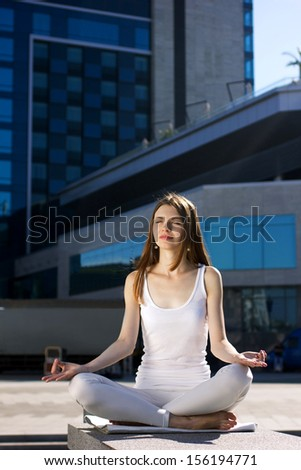 young woman sitting in yoga pose outdoors, on urban background - stock photo