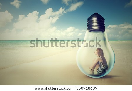 young woman sitting inside a light bulb on a beach looking at the ocean view. Loneliness outlier person. After storm survivor message to future generation concept