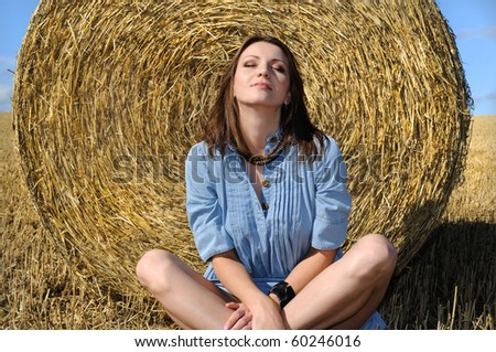 Young woman sitting near the straw bales - stock photo