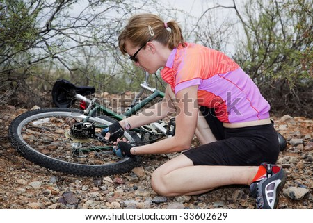 Young woman sitting next to and repairing mountain bike - stock photo
