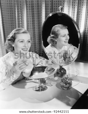 Young woman sitting next to mirror and holding a powder puff