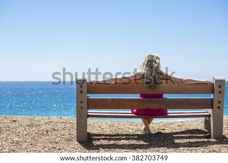 Young woman sitting on a bench and looking at the sea - stock photo