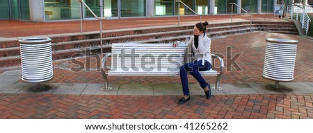 young woman sitting on a bench in a park - stock photo