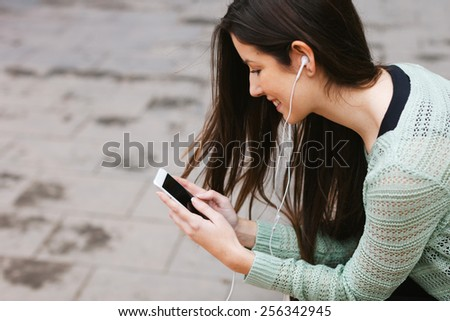 Young woman sitting on a bench in the city./ Young beautiful woman listening to music with phone in outdoors. - stock photo