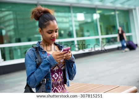 young woman sitting on a bench sending a text message - stock photo