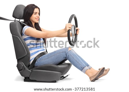 Young woman sitting on a car seat and holding a steering wheel isolated on white background - stock photo