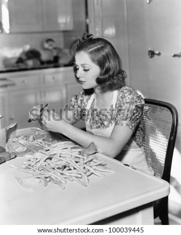 Young woman sitting on a chair and cutting beans - stock photo