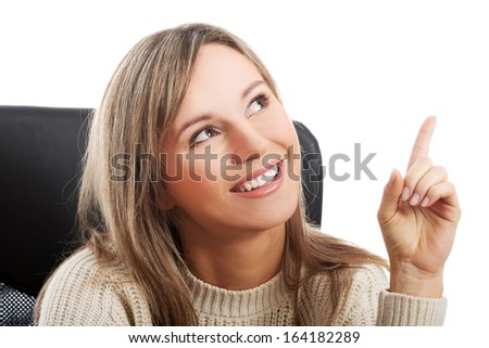 Young woman  sitting on a chair and pointing up. Isolated on white.  - stock photo