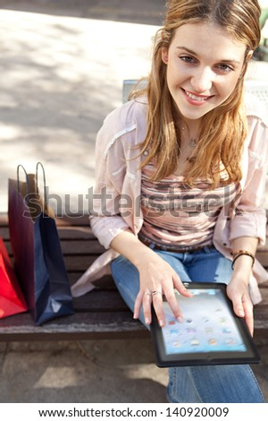 Young woman sitting on a city bench with her shopping bags, using a digital tablet pad and touching the screen while smiling at the camera during a sunny day. - stock photo